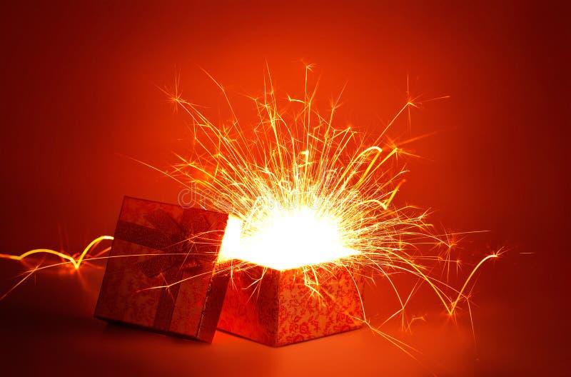 Abstrakt öppen guld- gåvaask och ljusfyrverkerijul på röd bakgrund, glad jul och lyckligt nytt år royaltyfria foton