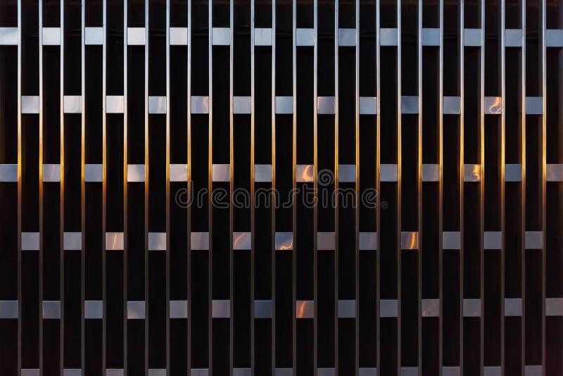 Abstrakt arkitektonisk detalj av vertikala linjer med fyrkanter av metall på solnedgången arkivfoto