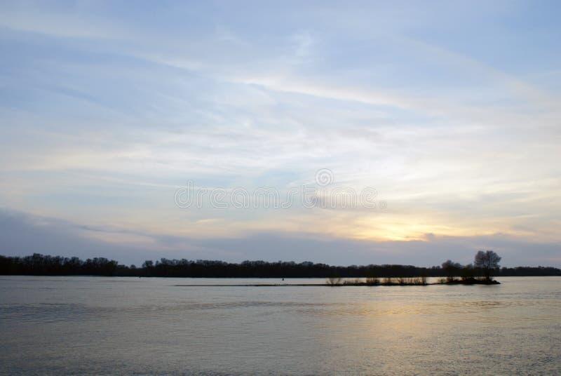 Abstrakt bakgrund av blå himmel med moln på solnedgången över floden arkivbild