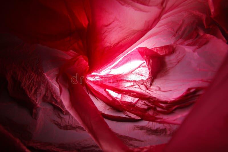 Abstrakt bakgrund av insidorna av en röd plastpåse arkivfoton
