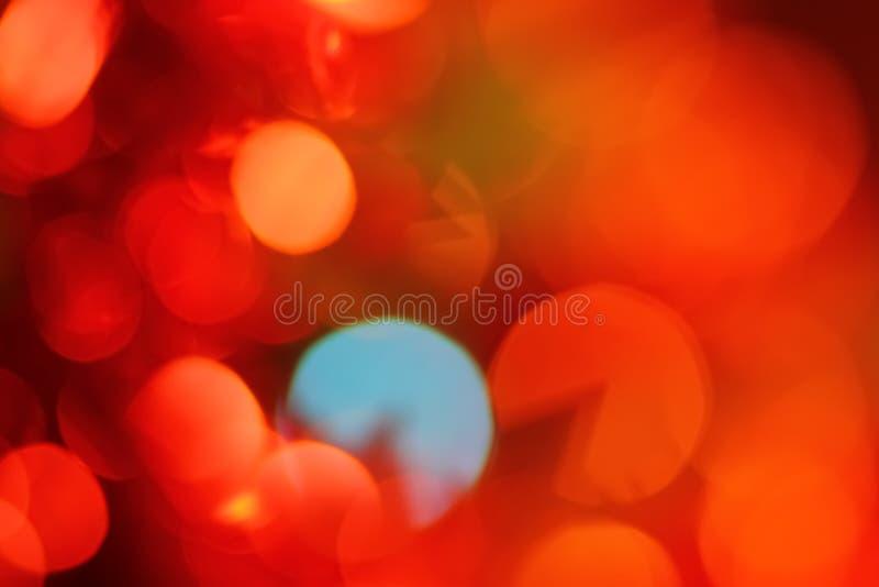 Abstrakt bakgrund av ljusa blänka ljus, för blåttguling för jul röd bokeh för ferie arkivfoto