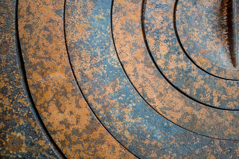 Abstrakt bakgrund av metall med geometriska hål i en cirkel och textur rostar apelsin-brunt med fläckar arkivbild