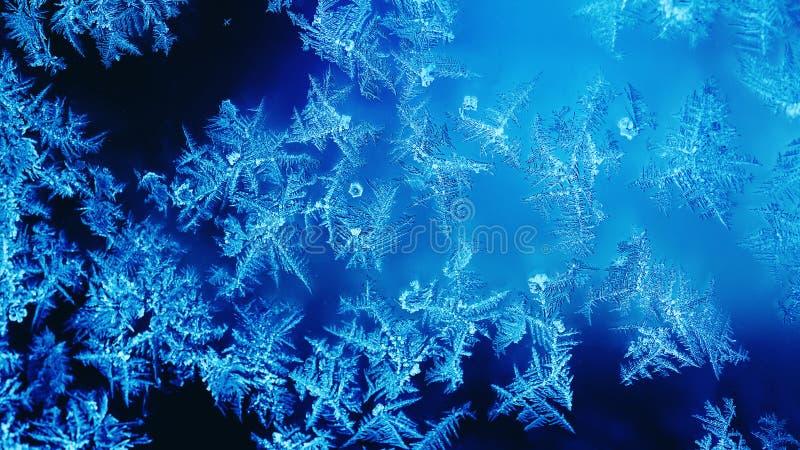 Abstrakt bakgrund för frostat djupfryst fönster Vintersäsongjul smyckar mörkt - den blåa tapeten för isfönstergarnering royaltyfri bild