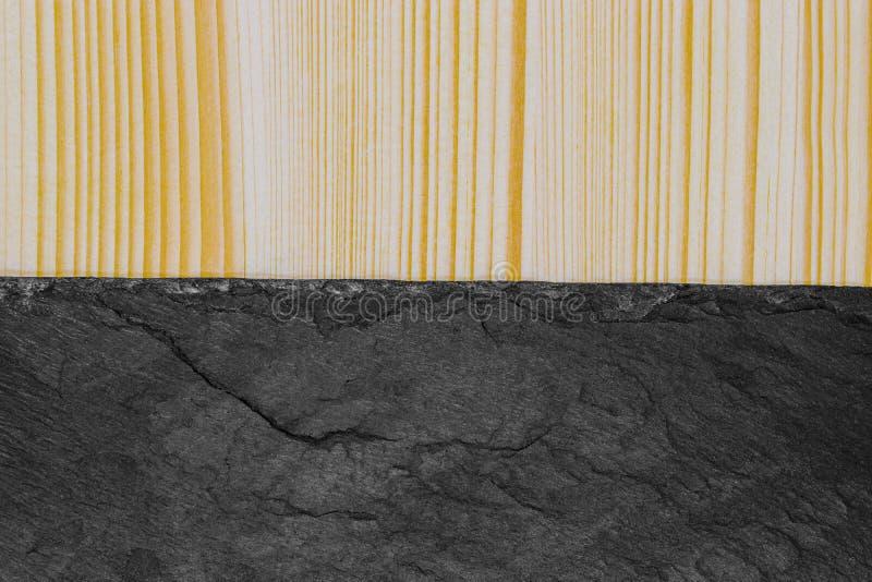 Abstrakt bakgrundssammansättning av delat i den halva randiga träplankan och den svarta stenen med kopieringsutrymme royaltyfri fotografi