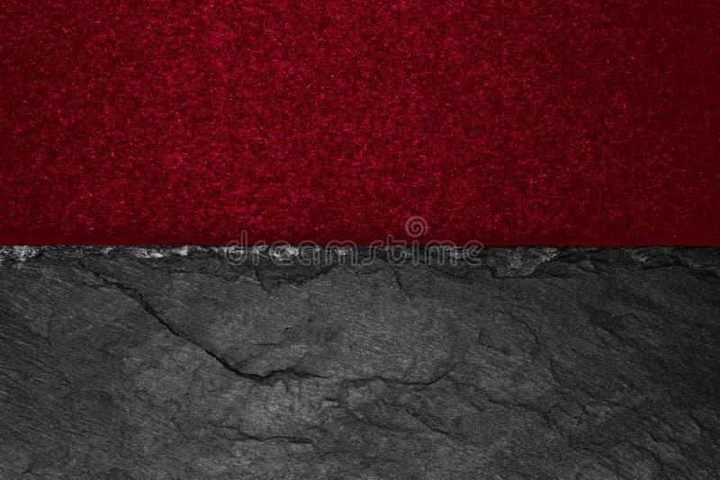 Abstrakt bakgrundssammansättning av delat i det halva matt livliga burgundy färgpapperet och den svarta stenen med kopieringsutry royaltyfria foton