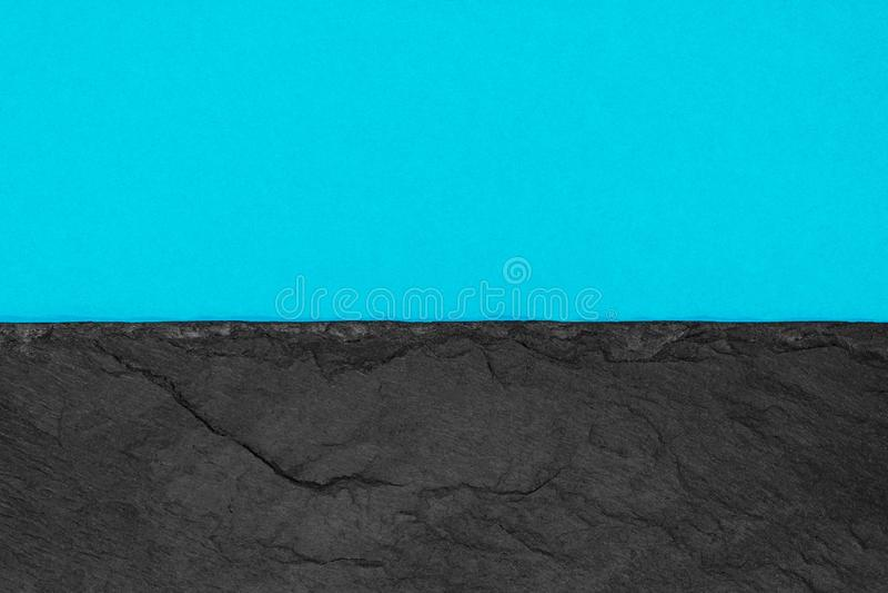 Abstrakt bakgrundssammansättning av delat i det matt livliga mjuka blåa färgpapperet för halva och den svarta stenen med kopierin arkivfoto