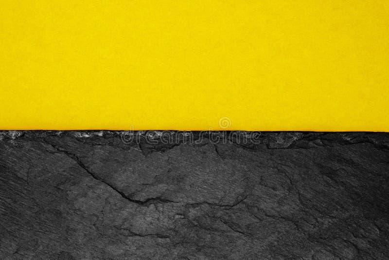 Abstrakt bakgrundssammansättning av delat i det matt mörka gula färgpapperet för halva och den svarta stenen med kopieringsutrymm royaltyfria foton