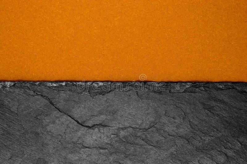 Abstrakt bakgrundssammansättning av delat i det matt mörkt för halva - orange färgpapper och svart sten med kopieringsutrymme arkivbilder