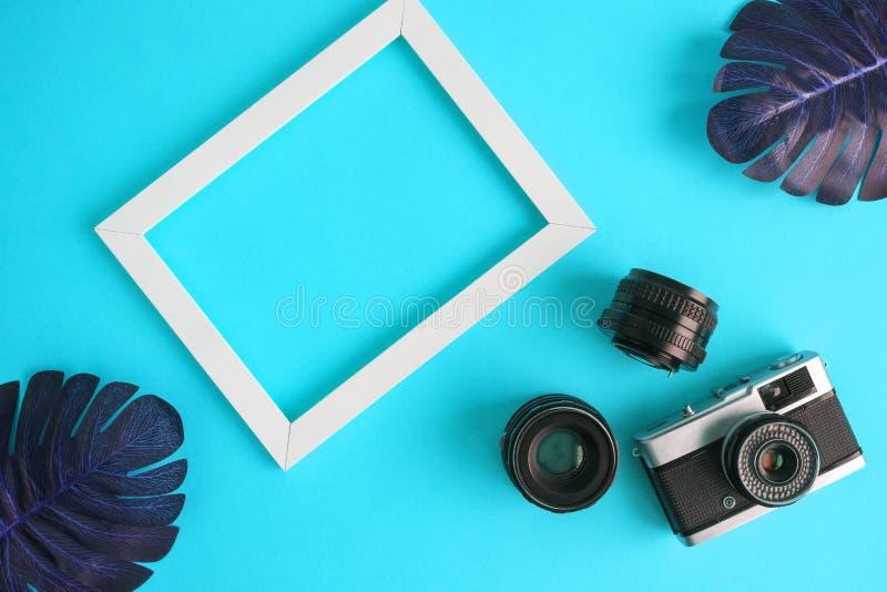 Abstrakt begrepp för fotoloppbakgrund med fotografiutrustning- och monsterasidor på blått royaltyfri fotografi