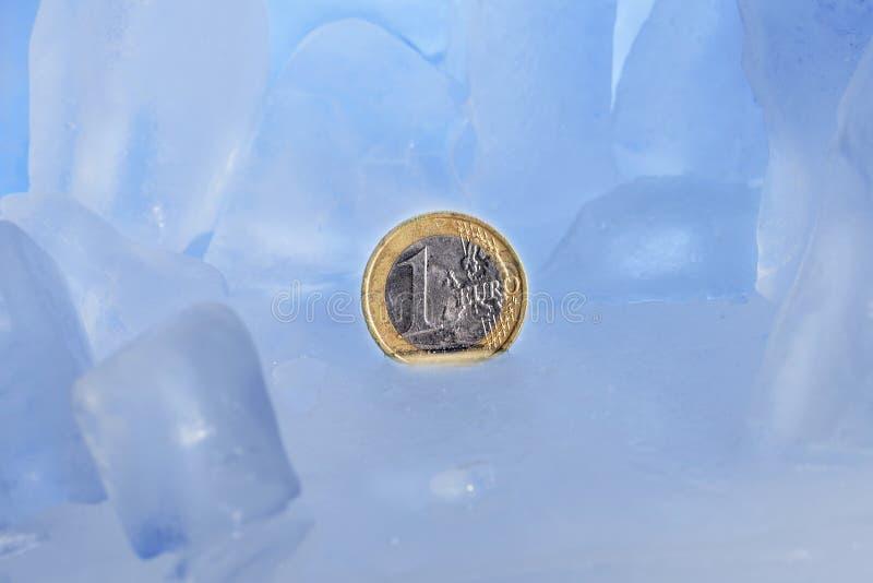 Abstrakt bild av djupfryst finans, 1 euromynt som frysas i blå is arkivbilder