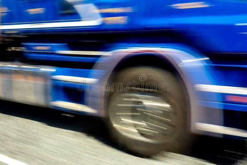 Abstrakt bild av en blå rusa lastbil med en stark effekt för rörelsesuddighet arkivbild