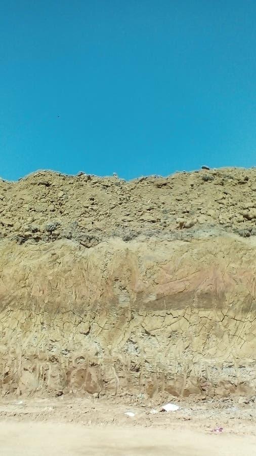 Abstrakt bild av olika lager av jord under den blåa himlen i ett pikområde arkivfoton
