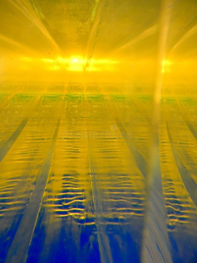 Abstrakt bild av två vätskor med olika tätheter som påverkar varandra med de Innehåller guld-, blåa gröna färger, har arkivbilder