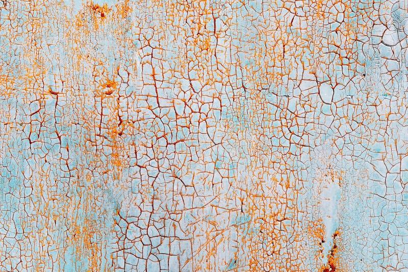 Abstrakt blå orange textur med grungesprickor Sprucken målarfärg på en metallyttersida