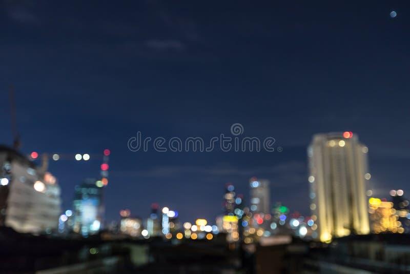 Abstrakt bokehbakgrund för Cityscape, Cityscape på skymningtid, suddigt foto som är defocused på den i stadens centrum nattljussi arkivfoton