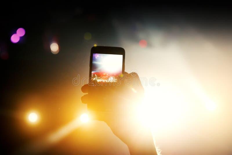 Abstrakt färgrik bakgrund av den hållande smartphonen för hand som fångar bildfotoet och rekordvideoen i händelse för konsertmusi arkivfoto