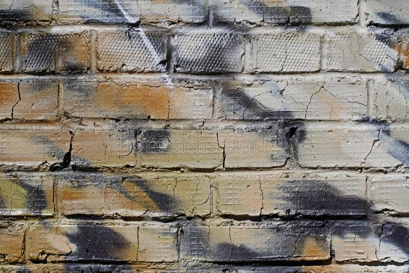 Abstrakt färgrik gräsplan-, vit-, beiga- och svarttegelstenvägg med sprickor royaltyfri bild