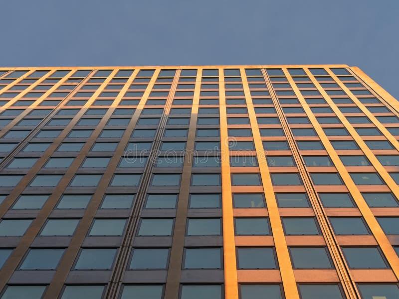 Abstrakt fragment av modern arkitektur Perspektivsikt för låg vinkel av mordern kontorsbyggnads yttersida med exponeringsglasföns royaltyfria foton