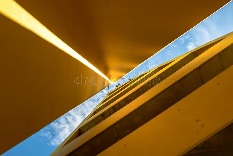 Abstrakt geometriskt arkitekturskott från botten upp med en strimma av ljust skina på en gul vägg royaltyfri bild