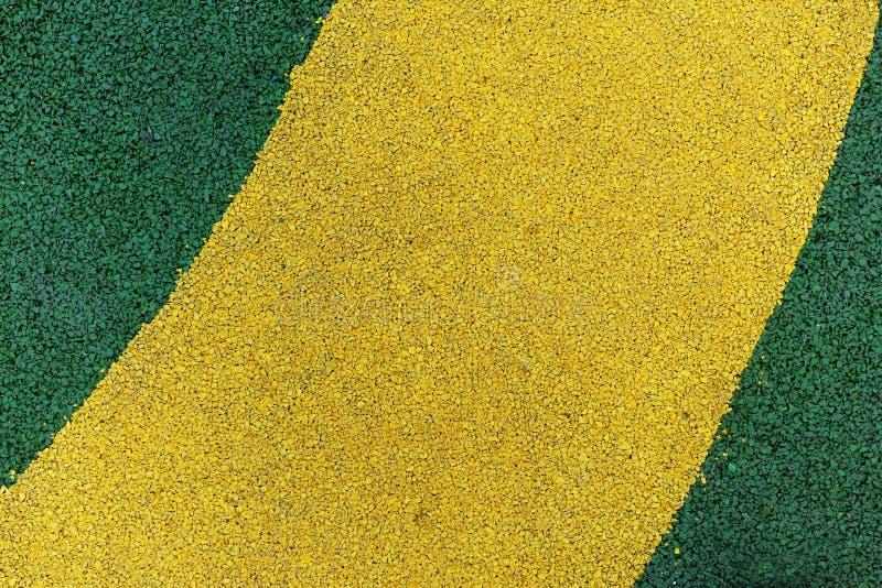 Abstrakt gul och grön målarfärg på asfalt arkivfoto