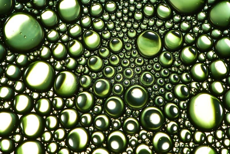 Abstrakt gulgocze jarzynowego olej na wodzie Zielony jaskrawy i odbijający tło zdjęcia stock