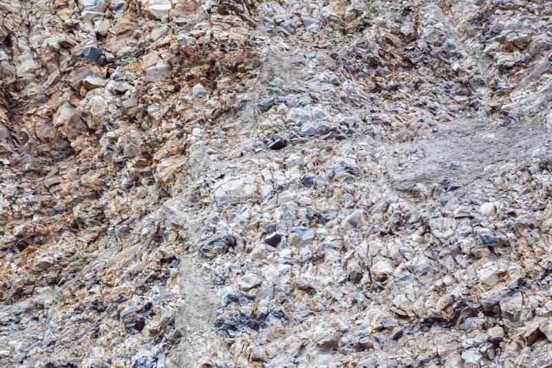 Abstrakt industriell bakgrund med texturen av yttersidan av en hög av den naturliga mång--färgade stenen, krossad sten, arkivbilder