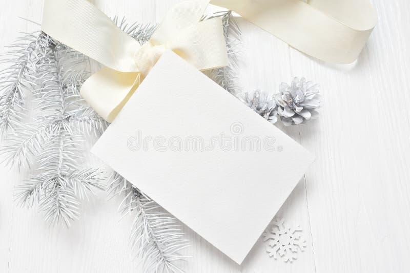 Abstrakt julbakgrund, vitt ark av papper som ligger bland små garneringar på det vita träskrivbordet Lekmanna- modell för lägenhe fotografering för bildbyråer