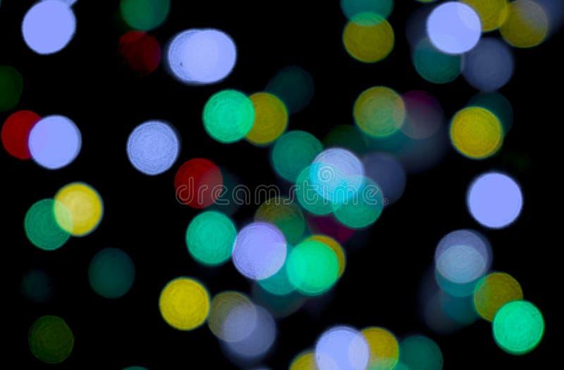 Abstrakt ljus bokeh som är färgrik på svart bakgrund genom att använda som en tapettaxture fotografering för bildbyråer