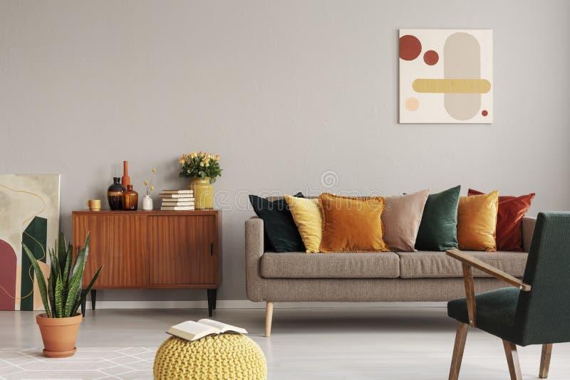 Abstrakt målning på den gråa väggen av retro vardagsrum som är inre med den beigea soffan med kuddar, tappningmörker - grön fåtöl arkivfoto
