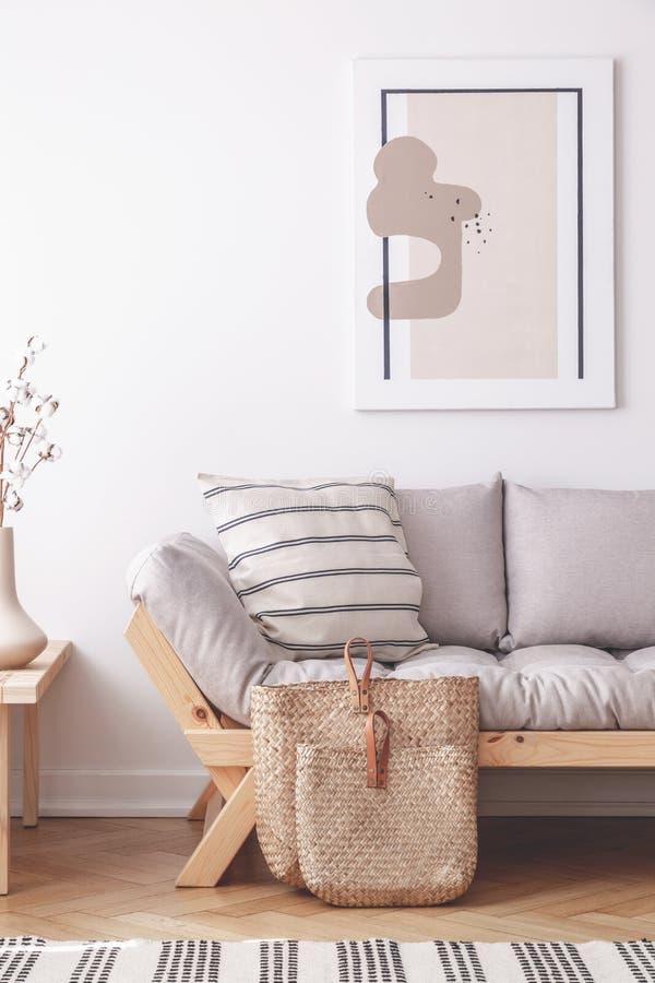 Abstrakt målning på väggen av naturlig beige vardagsrum med den gråa soffan i lagom inspirerade inre royaltyfria bilder