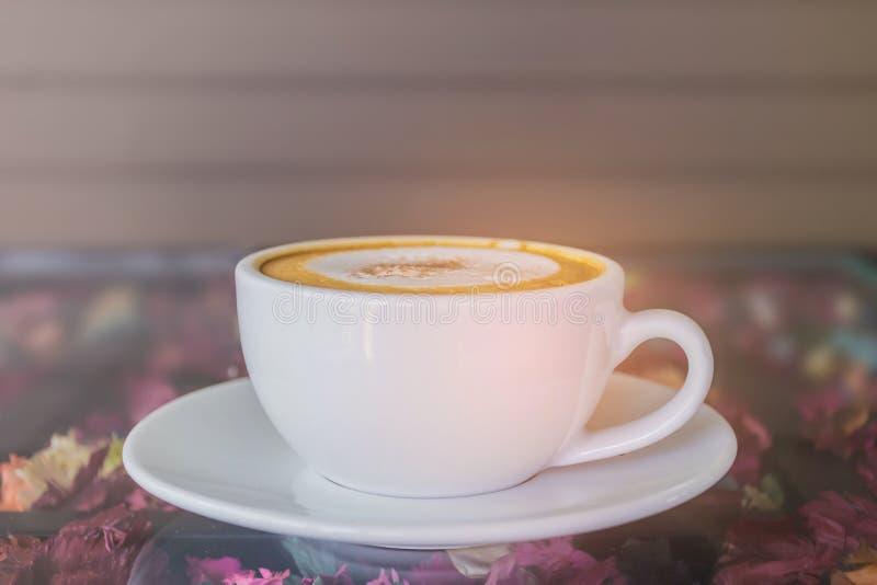 Abstrakt mjuk suddig och mjuk fokus per koppen av cappuccino, varmt kaffe med strålljuset, bakgrund för signal för linssignalljus arkivfoton