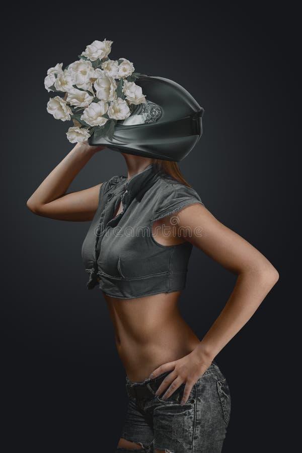 Abstrakt modestående av den unga kvinnan i motorcykelhjälm med blommor royaltyfria bilder