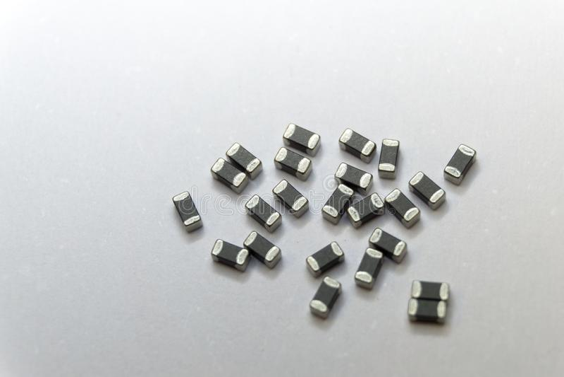 Abstrakt närbild av grått spritt 0402 delar för elektronik för makt för pärla för ferrite för chip för SMT yttersidamontering på  arkivbilder