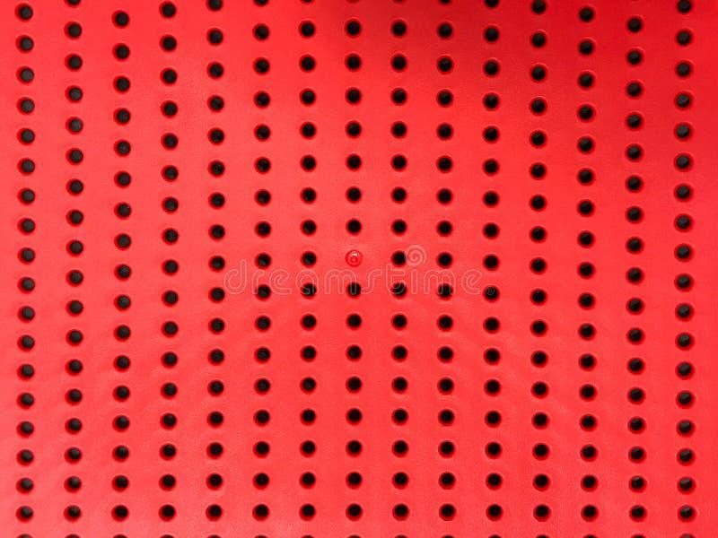 Abstrakt röd perforerad plast- bacground fotografering för bildbyråer