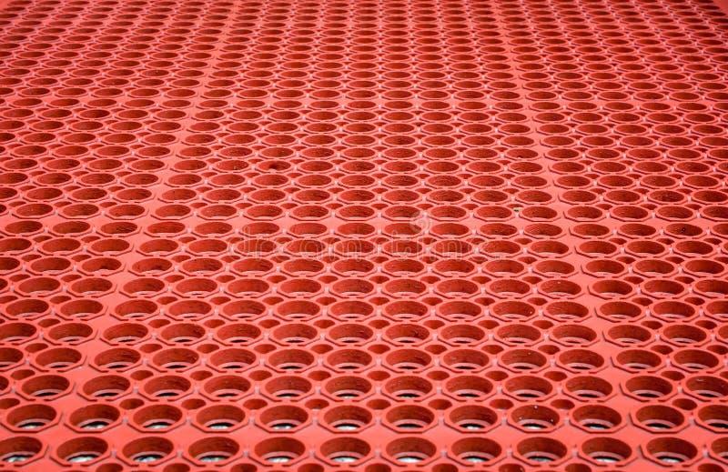 Abstrakt röd perforerad plast- bakgrund arkivbilder