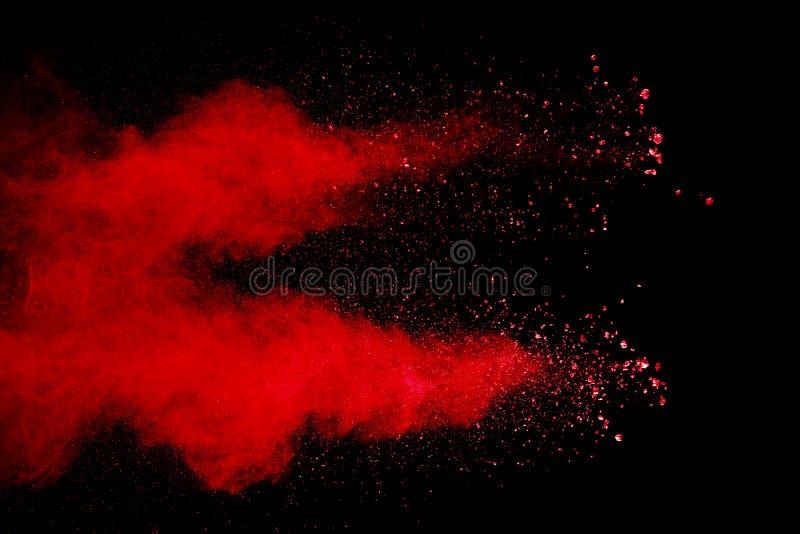Abstrakt rött damm stänkt på svart bakgrund royaltyfri foto