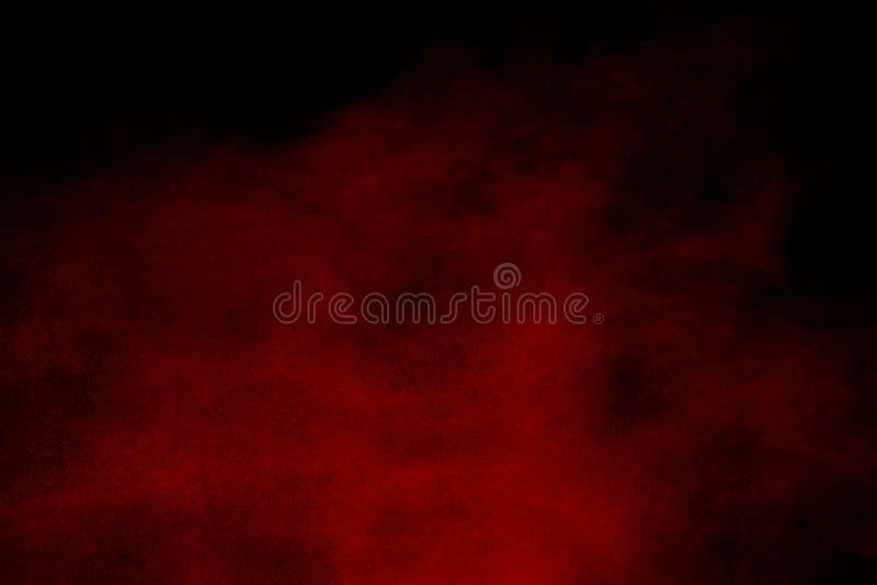 Abstrakt rött damm stänkt på svart bakgrund Röd pulverexplosion royaltyfria foton