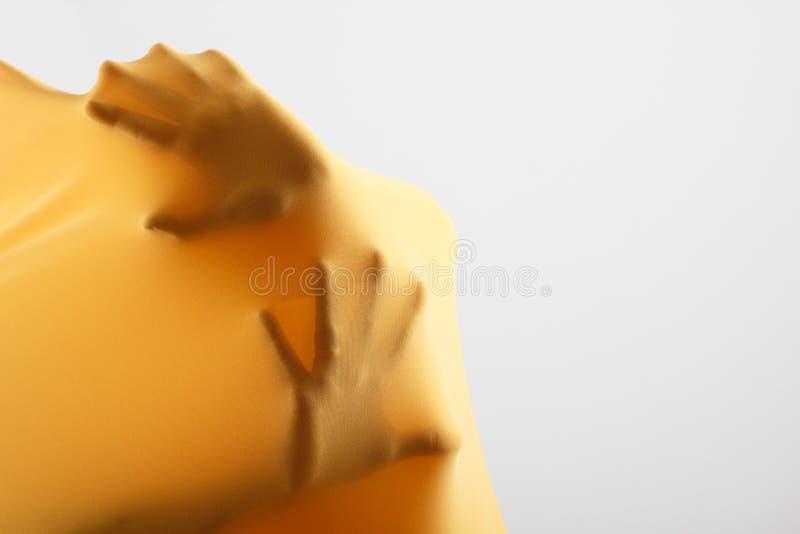 Abstrakt ręki, ludzka ręka wśrodku żółtej tkaniny zdjęcia stock