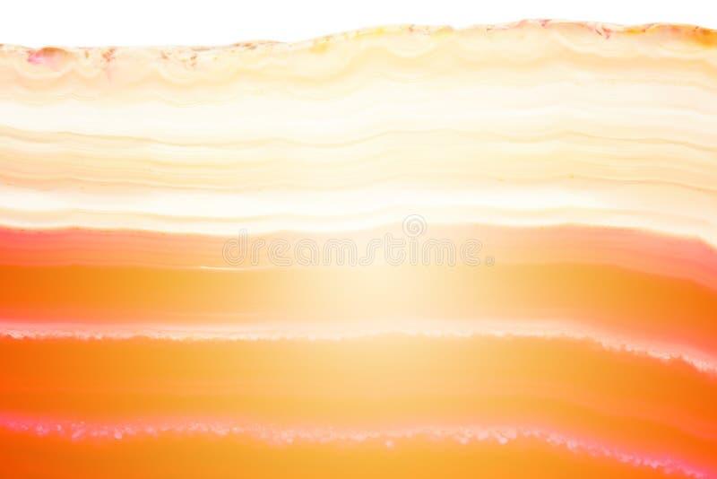 Abstrakt randigt mineraliskt tvärsnitt för för bakgrund, röd och orange agat med solstrålen arkivbilder