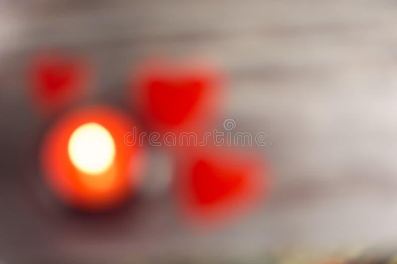 Abstrakt romanticbokeh av stearinljusljus och röda blured hjärtor arkivfoto