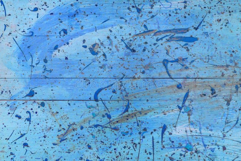 Abstrakt sikt av blåa träplankor med målarfärgfläckar som bakgrund, textur arkivbilder