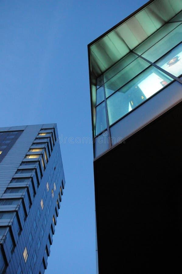 Abstrakt sikt av kontorsbyggnader på natten som uppåt ser med ljus i fönstren royaltyfri bild
