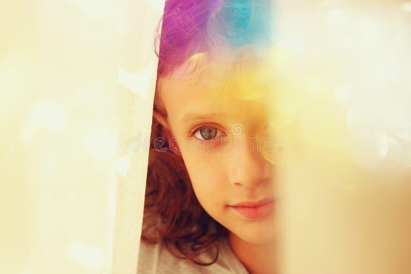 Abstrakt stående av den fundersamma lilla flickan nära fönster tappning filtrerad bild arkivbilder