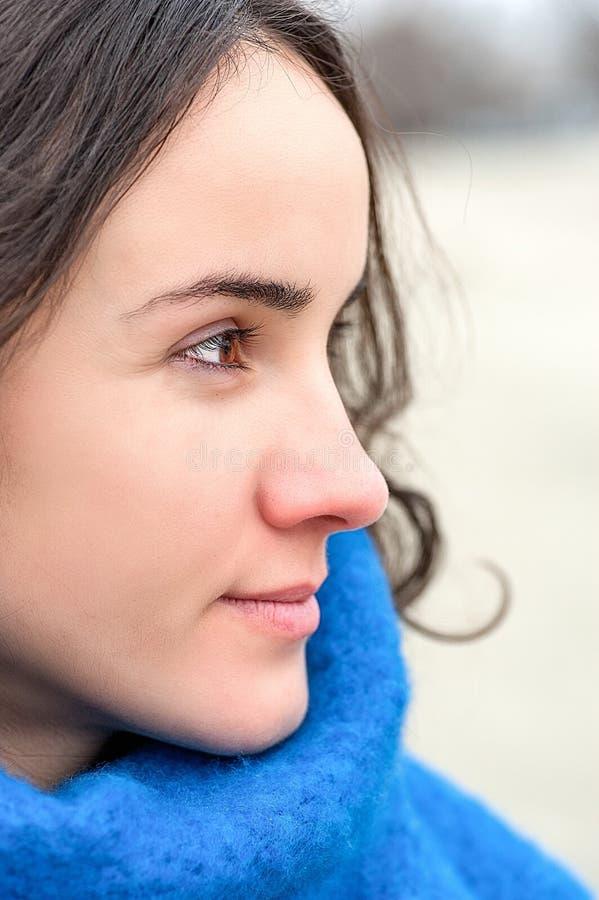 Abstrakt stående av den unga härliga flickan med ledsna och förtjusande ögon med känslig blick i den kalla dagen och den blåa hal arkivfoton