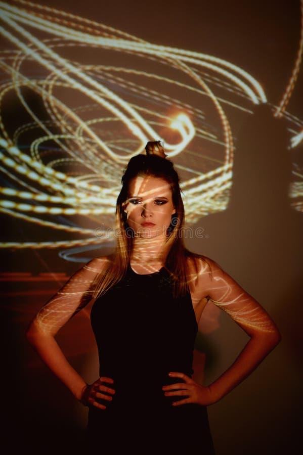 Abstrakt stående av en härlig flicka i ljuset av projektorn Varma orange skuggor Ljus kula Edison En känsla av arkivfoto