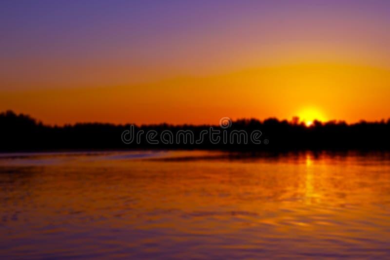 Abstrakt suddig bakgrund med sommarsjölandskap med guld- soluppgång Floden landskap Härligt landskap för suddighetsbokehljus royaltyfri foto