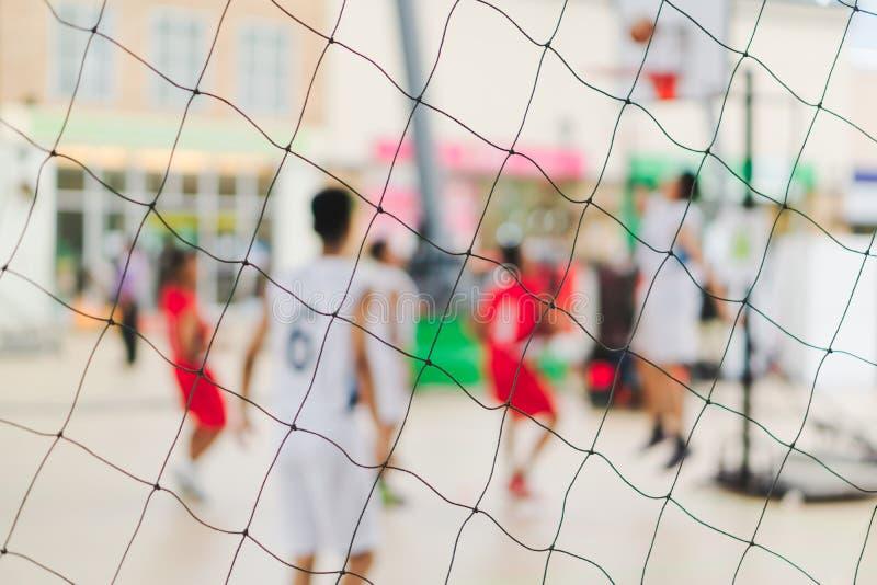 Abstrakt suddig bakgrundsgrupp av tonårs- folk som spelar gatabasket Fokusen på basketdomstolen förtjänar staketet för sport royaltyfri foto