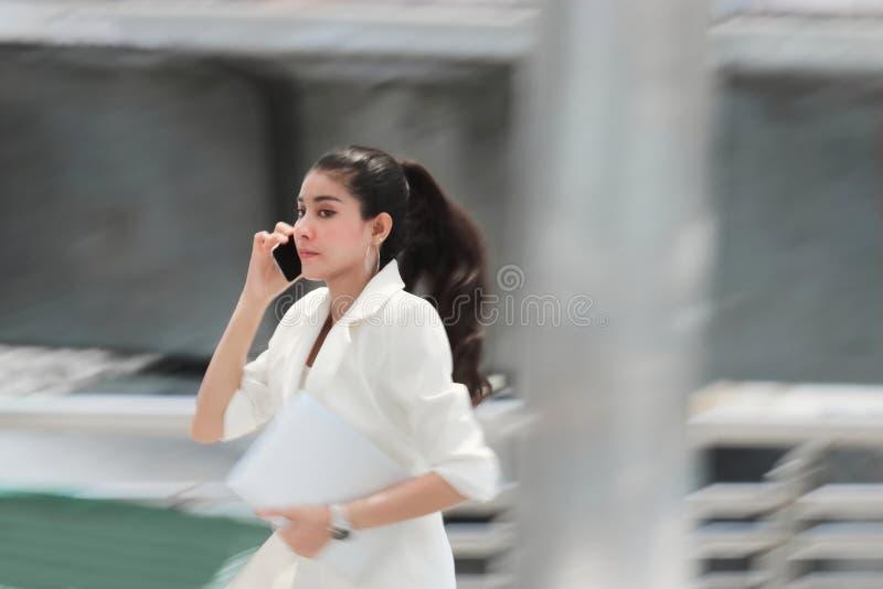 Abstrakt suddig rörelse av den unga asiatiska affärskvinnan som kör för att arbeta arkivfoton