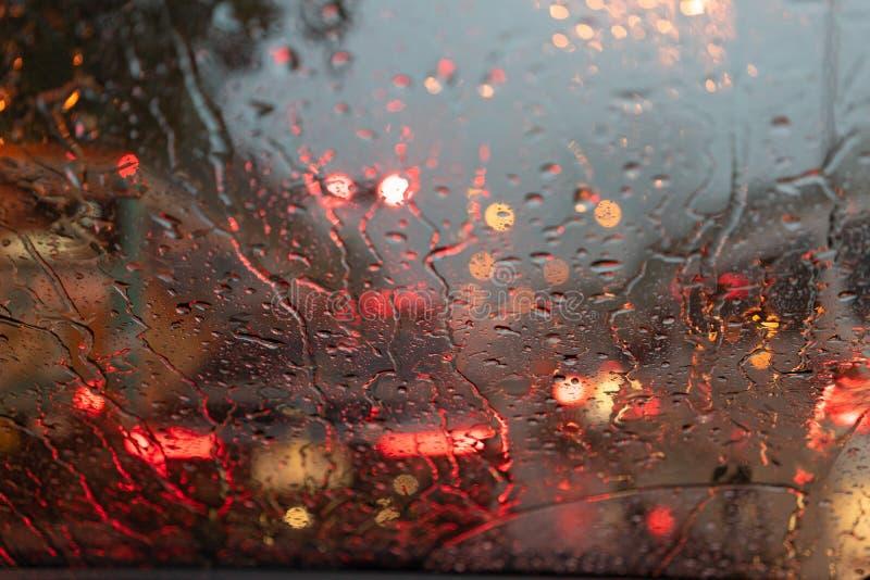 Abstrakt suddigt regn, medan bilen är i mitt av vägen på ljus för nattbilsvansen som reflekterar med regndroppar på bilen royaltyfri foto