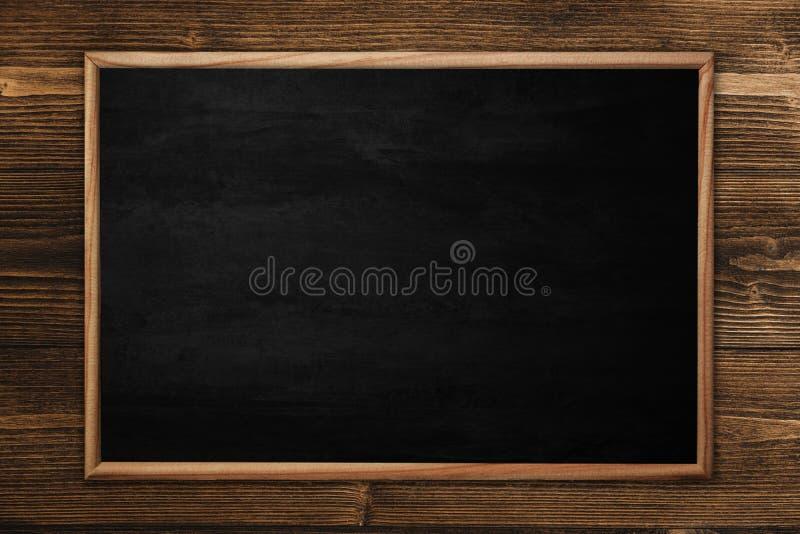 Abstrakt svart tavla eller svart tavla med ramen på träbakgrund royaltyfria foton